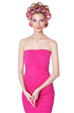 Woman in pink dress with hair curlers Royalty Free Stock Image
