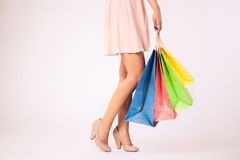 Woman in pink dress  holding colorful shopping bags Royalty Free Stock Photography