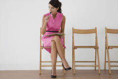 Woman In Pink Dress With Pen Looking Away Royalty Free Stock Photos