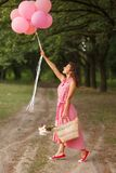 Woman in pink dress with pink balloons and wicker basket in green sunday park royalty free stock images