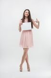 Woman in pink dress pointing on place copy. Emotional sweet young brunette woman standing in full length and pointing on copy place, isolated on white background Royalty Free Stock Photography
