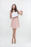 Woman in pink dress pointing on place copy. Emotional sweet young brunette woman standing in full length and pointing on copy place, isolated on white background Stock Photo