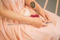 Woman in a pink dress put knitting needles and knitting threads on her knees. relaxed meditative dreamy hobby knitting Stock Photo