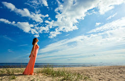 Woman in pink dress on seacoast Royalty Free Stock Photos
