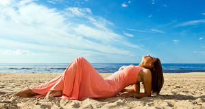 Woman in pink dress on seacoast Royalty Free Stock Images