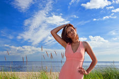 Woman in pink dress on seacoast Royalty Free Stock Photo