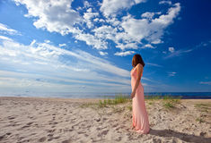 Woman in pink dress on seacoast Stock Photo