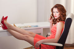 Woman in pink dress sits at a desk with his feet up on the desk. Businesswoman in pink dress sits at a desk stock photography