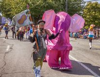 Woman With Pink Elephant. SEATTLE, WA - JUNE 22, 2013: An unidentified woman in a steampunk costume appears to be leading a pink elephant through the street Stock Photography