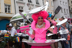 Woman in pink fancy costume with cutlery in the back Stock Photography