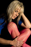Woman in pink fishnet cross legged look down close Stock Photography