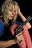 Woman in pink fishnet stockings hold gun look at pistol Stock Images