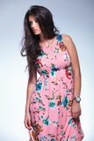 Woman in pink floral dress is looking to her side Stock Photos