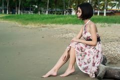 Woman in Pink Floral Halter Dress Seating in Driftwood Royalty Free Stock Images