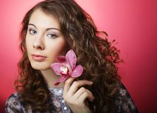 Woman with pink flower over pink background. Young curly woman with pink flower over pink background Stock Image