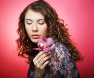 Woman with pink flower over pink background Royalty Free Stock Photos