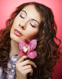 Woman with pink flower over pink background Royalty Free Stock Images