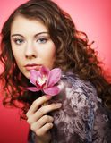 Woman with pink flower over pink background Royalty Free Stock Image