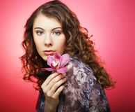 Woman with pink flower over pink background. Young curly woman with pink flower over pink background Royalty Free Stock Photography