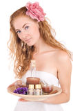 Woman with pink flower and spa products Royalty Free Stock Photos