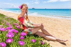 Woman with pink flowers on sandy beach with blue sea Royalty Free Stock Photo