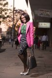 Woman in Pink Formal Coat and Green and Gray Dress With Black Hand Bag Royalty Free Stock Photography