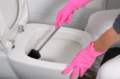 Woman in pink gloves cleaning the toilet Stock Photos