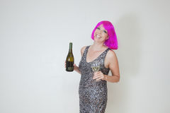 Woman with pink hair and bottle of wine Stock Photos