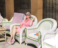 The woman in the pink has a rest in a chair Stock Image