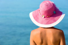 Woman with pink hat looking at the sea Stock Image