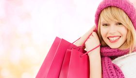 Woman in pink hat and scarf with shopping bags Royalty Free Stock Photography