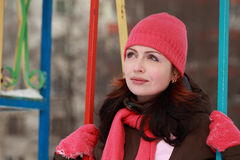 Woman in pink hat sitting on swing in winter Royalty Free Stock Images