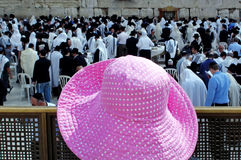 Woman Pink Hat at Western Wall. A woman in a pink hat looks on as the Cohenim men or Jewish Priests take part in a mass prayer and blessing for the Jewish people Royalty Free Stock Photography