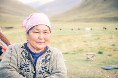 Woman with pink headcloth in Kyrgyzstan. South Inylchek Glacier, Kyrgyzstan - circa August 2011: Old native woman with pink headcloth with beautiful humble smile Royalty Free Stock Photography
