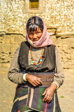 Woman with pink headcloth in Nepal. Dolpo, Nepal - circa June 2012: Black-haired woman in brown dress with pink headcloth wears colourful necklace made of beads Stock Photography