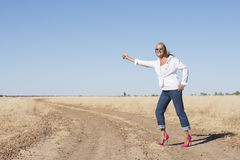 Woman in pink high heels hitchhiking in rural area Stock Photo