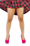 Woman pink high heels and plaid skirt. Young woman reveals her legs by lifting up her plaid skirt Stock Photo