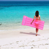 Woman with pink inflatable raft at the beach Royalty Free Stock Photography