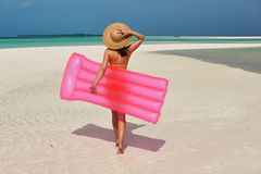 Woman with pink inflatable raft at the beach Stock Photography