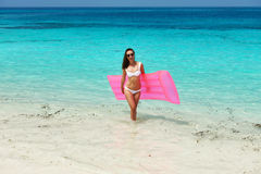 Woman with pink inflatable raft at the beach Stock Image