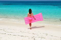Woman with pink inflatable raft at the beach Stock Images