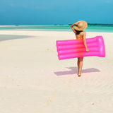 Woman with pink inflatable raft at the beach Royalty Free Stock Photos