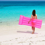 Woman with pink inflatable raft at the beach Royalty Free Stock Image