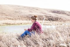 Woman in Pink Jacket Sitting on a Grass Field Stock Photos