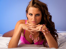 Woman in pink lingerie lying in bed on silk sheets Royalty Free Stock Photography