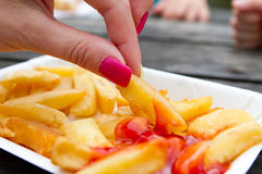 Woman with pink nails eating chips Royalty Free Stock Image