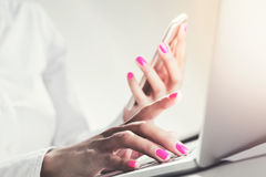 Woman with pink nails holding smartphone, typing Stock Photos