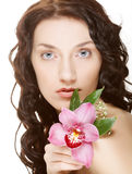 Woman and pink orchid Stock Photography