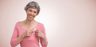 Composite image of woman in pink outfits showing ribbon for breast cancer awareness stock photography