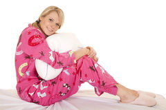 Woman pink pajamas sit hold pillow look. A woman in her pajamas with a smile on her face, holding on to her pillow Stock Photography